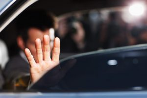 Man's hand blocking paparazzi from car