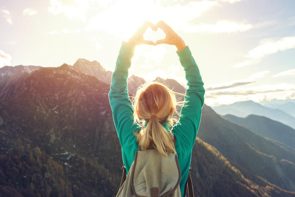 Girl hand heart shape peak of mountain
