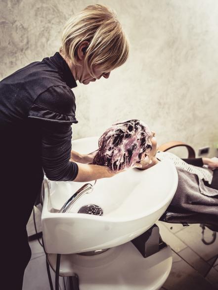 Friseurin wäscht Frau Haare