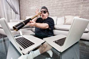Mann mit Fernglas und Fliegerbrille schaut auf MacBook
