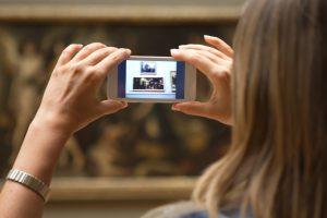 Frau fotografiert mit Smartphone Bild im Museum ab