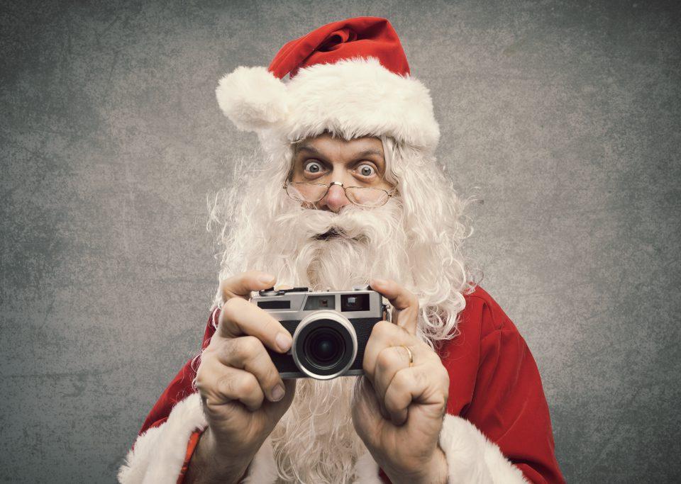 Weihnachtsmann mit Fotokamera in der Hand