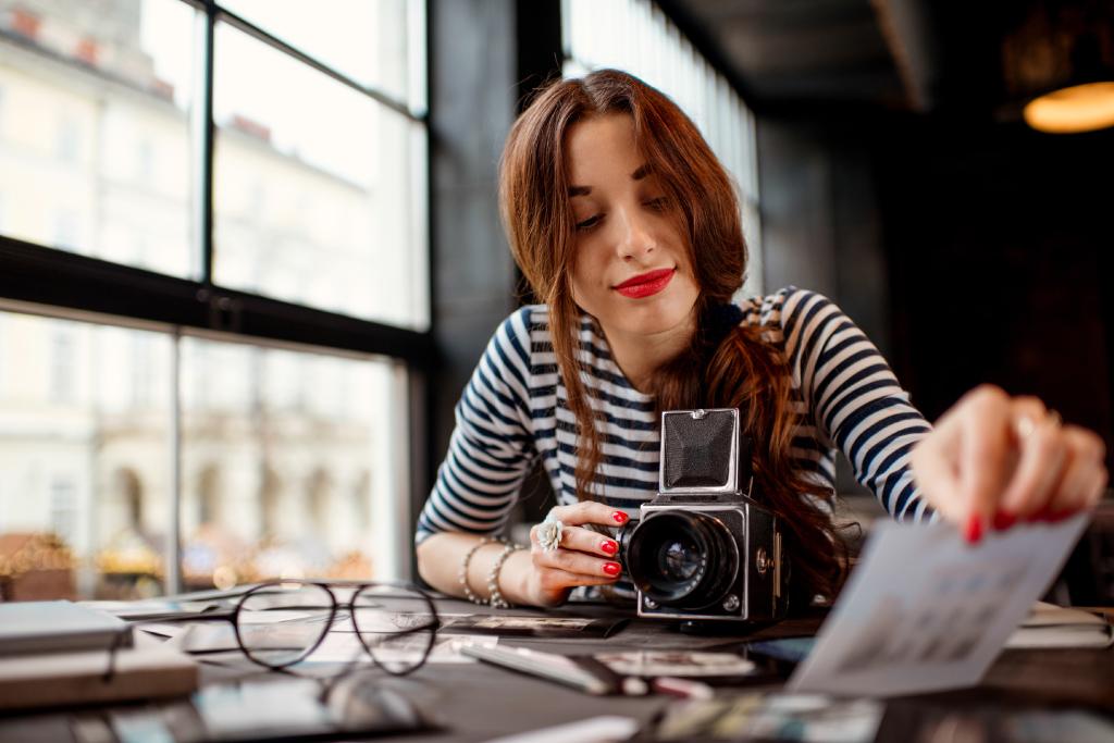 Frau mit Kamera schaut Fotos an