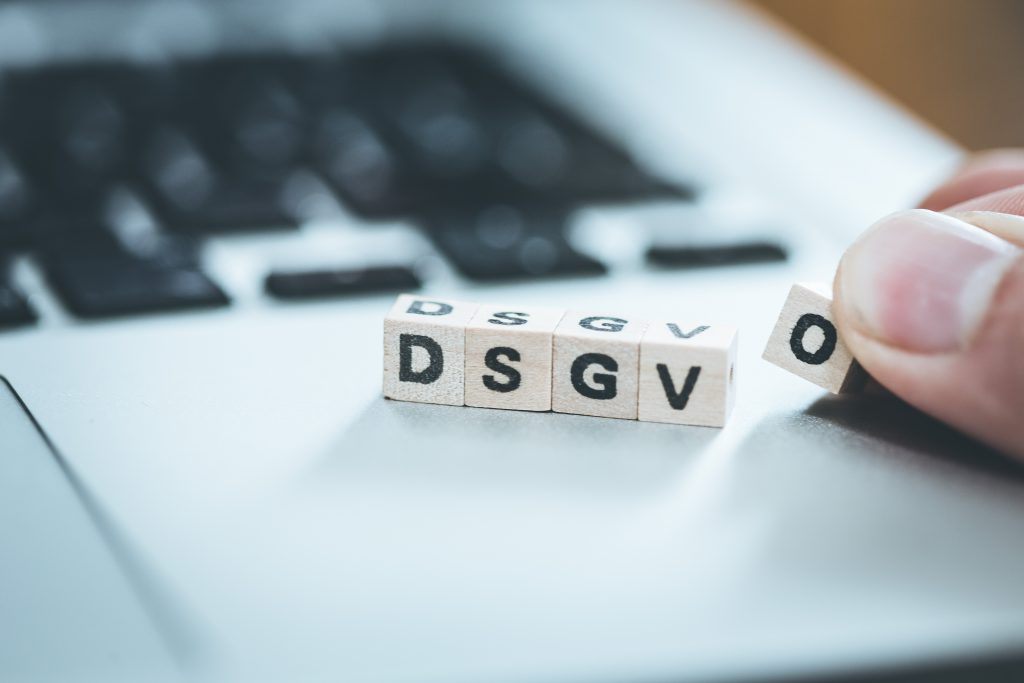 "Dsgvo: Wooden Cubes With Letters ""dsgvo"" Lying On A Laptop. Datenschutzgrundverordnung."