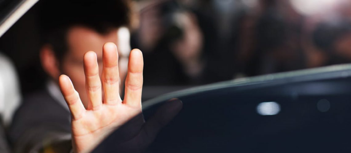 Man's hand blocking paparazzi from car
