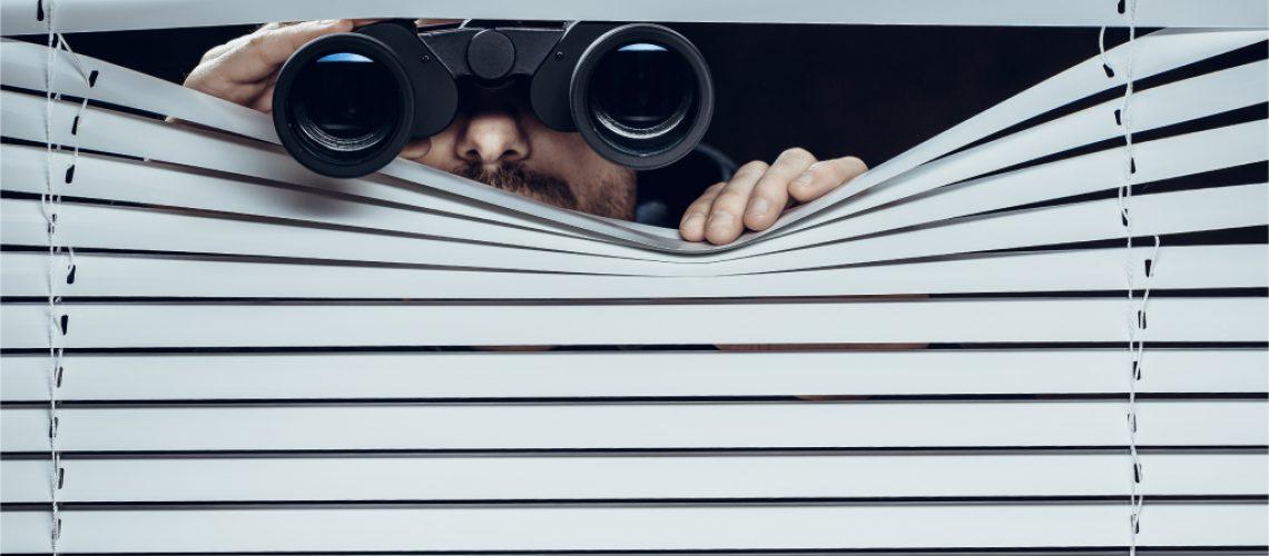 Mann schaut mit Fernglas durch Jalousie