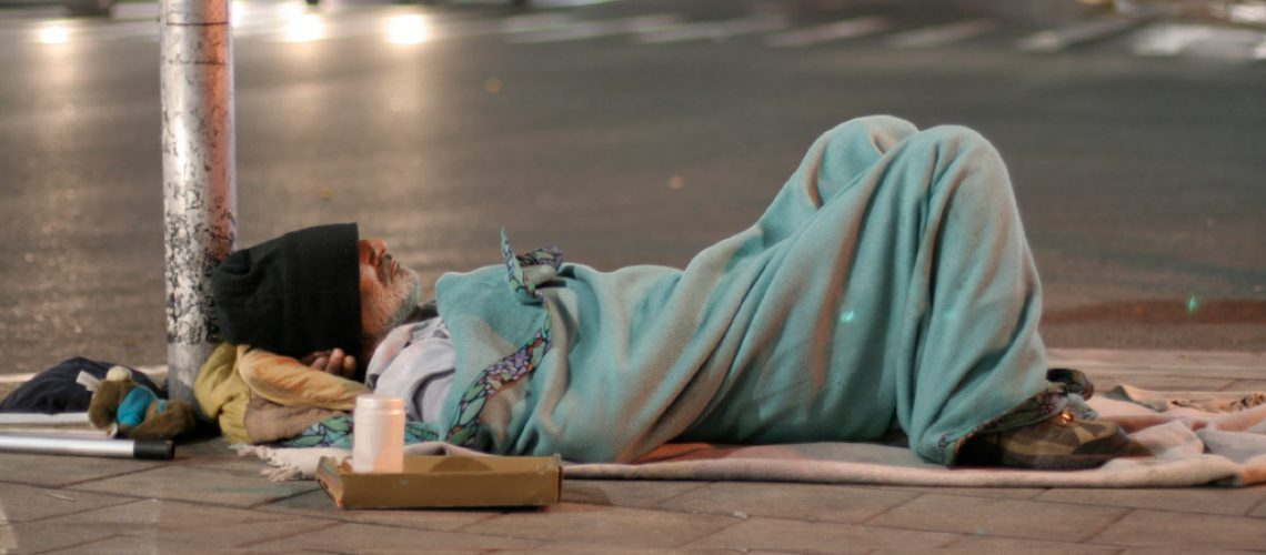 Homeless man sleeping in the street in UK being photographed in public