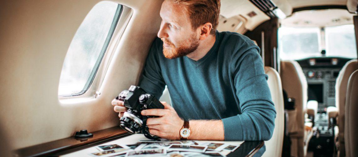 Fotograf schaut aus Flugzeugfenster